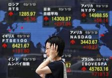 Женщина проходит мимо брокерской конторы в Токио 5 июля 2013 года. Азиатские фондовые рынки снизились в четверг на фоне квартальной отчетности компаний и локальных факторов. REUTERS/Toru Hanai