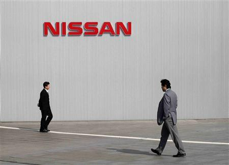 Men walk past a Nissan Motor Co logo at the company's global headquarters in Yokohama, south of Tokyo in this February 9, 2011 file photo. REUTERS/Toru Hanai/Files
