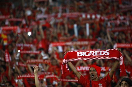Indonesian Liverpool supporters hold scarves during a friendly soccer match between Liverpool FC and the Indonesian national team at Gelora Bung Karno Stadium in Jakarta July 20, 2013. REUTERS/Beawiharta