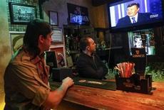 Посетители паба в Киеве смотрят выступление президента Украины Виктора Януковича 22 февраля 2013 года. Вынашиваемые правительством Украины налоговые новации помогут пополнить опустевшую из-за рецессии казну в преддверии президентских выборов, на которые нацелился действующий глава государства, но чреваты замедлением ВВП, считают экономисты и предприниматели. REUTERS/Sergii Polezhaka