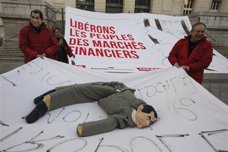 Members of the Front de Gauche political party hold a sheet with a puppet figure in the likeness of France's President Nicolas Sarkozy during a protest demonstration on the eve of traditional carnival festivities in Nice February 17, 2012. REUTERS/Eric Gaillard