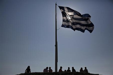 Tourists stand under a Greek flag atop the hill of the Acropolis in Athens July 3, 2013. REUTERS/Yorgos Karahalis