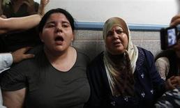 Дочь и жена убитого в Тунисе оппозиционного политика Мохамеда Брами оплакивают его гибель 25 июля 2013 года. Убийство лидера оппозиции в Тунисе вывело на улицы тысячи людей. REUTERS/Zoubeir Souissi