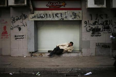 A boy rests in front of a closed shop at Tahrir Square in Cairo January 16, 2013. REUTERS/Suhaib Salem
