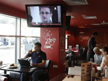 A television screen shows former U.S. spy agency contractor Edward Snowden during a news bulletin at a cafe at Moscow's Sheremetyevo airport July 24, 2013. REUTERS/Tatyana Makeyeva