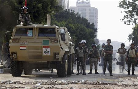 Army soldiers take positions in front of members of the Muslim Brotherhood and supporters of deposed Egyptian President Mohamed Mursi at Republican Guard headquarters in Nasr City, a suburb of Cairo July 19, 2013. REUTERS/Amr Abdallah Dalsh