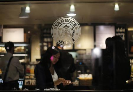 A woman prepares her drink in a Starbucks store in New York in this file photo from June 25, 2013. REUTERS/Brendan McDermid /Files
