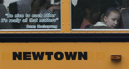 Students sit behind a quote by slain Sandy Hook Elementary School principal Dawn Hochsprung, displayed on the window of a school bus, as it approaches a stop near the original site of Sandy Hook Elementary School in Newtown, Connecticut June 14, 2013. REUTERS/Adrees Latif