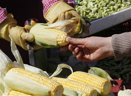 A woman looks at an ear of corn before buying it from a vendor (L) at a morning market in Beijing April 8, 2013. REUTERS/Kim Kyung-Hoon