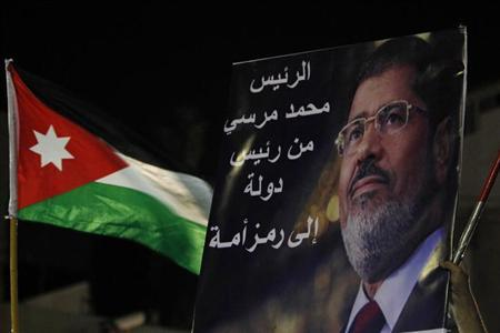 A poster of deposed Egyptian President Mohamed Mursi and a Jordanian national flag are held up by Islamists and members of the Egyptian community in Jordan during a demonstration against Mursi's ousting in front of the Egyptian embassy in Amman July 26, 2013. REUTERS/Muhammad Hamed