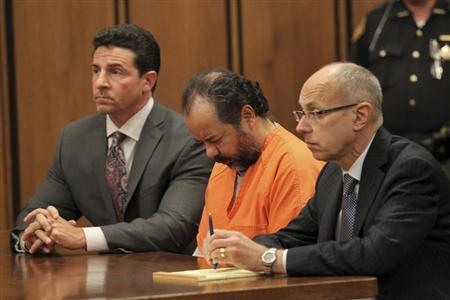 Ariel Castro, 52, sits with his head down between his attorneys Jaye Schlachet (R) and Craig Weintraub (L) during his pre-trial hearing on charges including rape, kidnapping and murder in Cleveland, Ohio June 19, 2013. REUTERS/Aaron Josefczyk