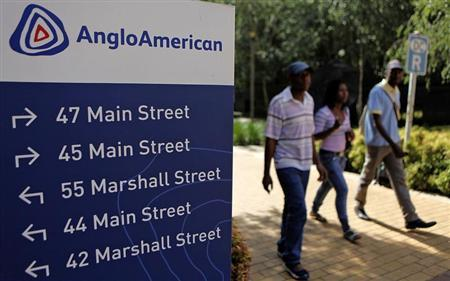 People walk past a board outside the Anglo American offices in Johannesburg January 8, 2013. REUTERS/Siphiwe Sibeko
