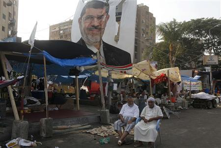 Supporters of deposed President Mohamed Mursi sit near a poster depicting Mursi around the Raba El-Adwyia mosque square in Cairo July 24, 2013. REUTERS/Asmaa Waguih