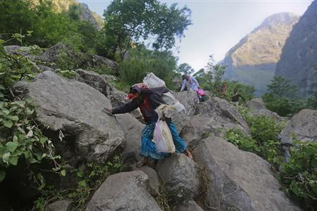 A woman carrying her belongings in cement sacks climbs down a hill during a rescue operation at Govindghat in the Himalayan state of Uttarakhand June 22, 2013. REUTERS/Danish Siddiqui/Files