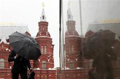 Мужчина с зонтом идет по Красной площади в Москве 18 мая 2011 года. Прохладная и дождливая погода сохранится в российской столице на выходных, ожидают синоптики. REUTERS/Denis Sinyakov