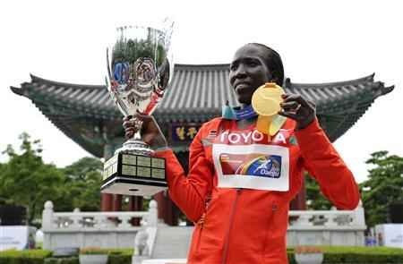 Edna Kiplagat of Kenya holds up her gold medal and the trophy presented to the winning team after the women's marathon final at the IAAF World Championships in Daegu August 27, 2011. REUTERS/Dylan Martinez