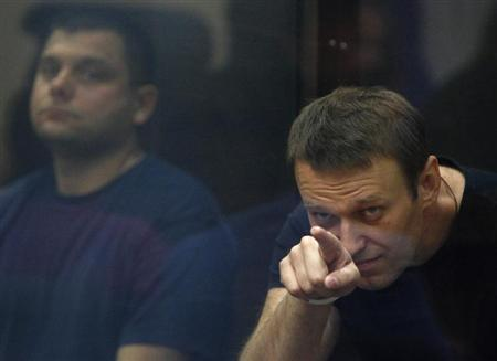 Russian protest leader Alexei Navalny (R) and his co-defendant Pyotr Ofitserov sit in a glass-walled cage during a court session in Kirov, July 19, 2013. REUTERS/Sergei Karpukhin