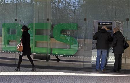 People use an ATM machine outside the headquarters of Portuguese bank Banco Espirito Santo (BES) in Lisbon February 3, 2012. REUTERS/Jose Manuel Ribeiro