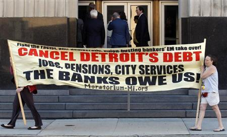 Protesters carry a banner calling for Detroit's debt to be cancelled as people enter the federal courthouse for day one of Detroit's municipal bankruptcy hearings in Detroit, Michigan July 24, 2013. REUTERS/ Rebecca Cook