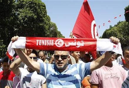 A supporter of the Islamist Ennahda movement holds up a scarf as he chants slogans during a demonstration in Tunis July 26, 2013. REUTERS-Zoubeir Souissi