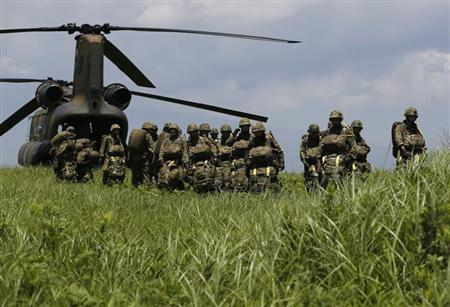 Japanese Ground Self-Defense Force's 1st Airborne Brigade soldiers prepares to board a CH-47 helicopter for a parachute drop training during their military drill at Higashifuji training field in Susono, west of Tokyo, July 8, 2013. REUTERS/Issei Kato