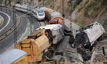 A passenger train drives past the site of a train crash, with the train engine (R) derailed from the track, in Santiago de Compostela, northwestern Spain, July 27, 2013. REUTERS/Miguel Vidal