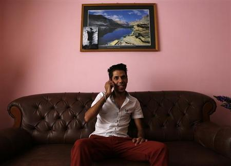 Naser Gulzad, 25, conducts business on the phone in his Kabul home July 25, 2013. REUTERS/Mohammad Ismail