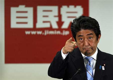 Japan's Prime Minister and the leader of the ruling Liberal Democratic Party (LDP), Shinzo Abe, points to a reporter during a news conference following a victory in the upper house elections by his ruling coalition, at the LDP headquarters in Tokyo July 22, 2013. REUTERS/Issei Kato