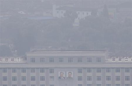 Portraits of late North Korean leaders Kim Jong-il and Kim Il-sung (L) are seen amid the morning fog and rain in Pyongyang July 28, 2013. REUTERS/Jason Lee