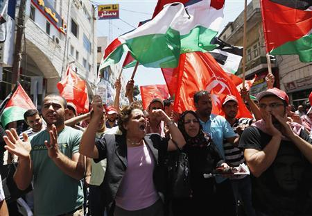 Palestinians wave Palestinian and Popular Front for the Liberation of Palestine (PFLP) flags during a protest against the renewal stalled peace talks with Israel, in the West Bank city of Ramallah July 28, 2013.REUTERS/Mohamad Torokman