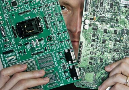 Security researcher Charlie Miller holds two automobile electronic control module circuit boards while posing in his home-office in Wildwood, Missouri, April 30, 2013. REUTERS/Sarah Conard