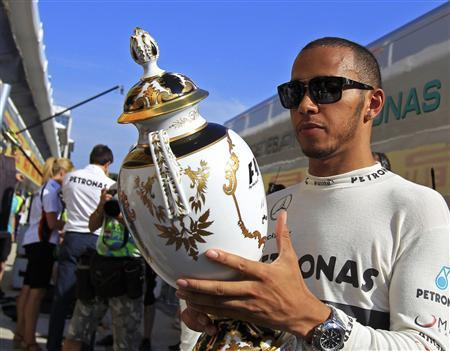Mercedes Formula One driver Lewis Hamilton of Britain looks at his trophy after winning the Hungarian F1 Grand Prix at the Hungaroring circuit in Mogyorod, near Budapest July 28, 2013. REUTERS/Bernadett Szabo