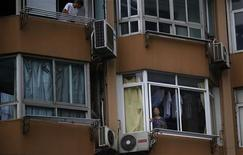 A woman stands next to her apartment window in downtown Shanghai July 26, 2013. REUTERS/Carlos Barria