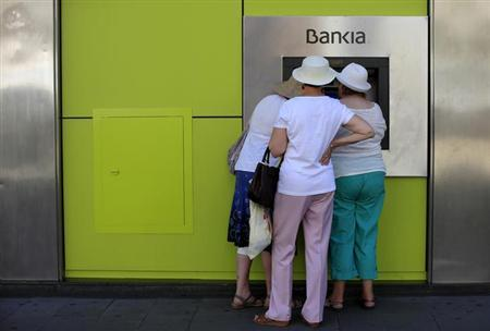 People use an ATM machine at a branch of Spain's nationalized lender Bankia in the Andalusian capital of Seville, southern Spain, June 24, 2013.REUTERS/Marcelo del Pozo