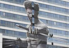 """Рабочий устанавливает плакат с изображением Хью Джекмана в роли Росомахи на здании в Бангкоке 9 июля 2013 года. """"Росомаха: Бессмертный"""" с Хью Джекманом в роли когтистого супергероя комиксов Marvel стартовала с первого места в прокате Северной Америки, но ее результаты оказались значительно слабее прогноза. REUTERS/Chaiwat Subprasom"""