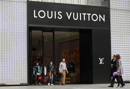 Shoppers walk past a Louis Vuitton store in Shanghai in this March 8, 2011 file photo. REUTERS/Aly Song