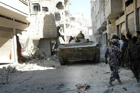 Forces loyal to Syria's President Bashar al-Assad are seen at al Khaldia neighbourhood in Homs city, in this handout photograph distributed by Syria's national news agency SANA on July 27, 2013. REUTERS/SANA/Handout via Reuters