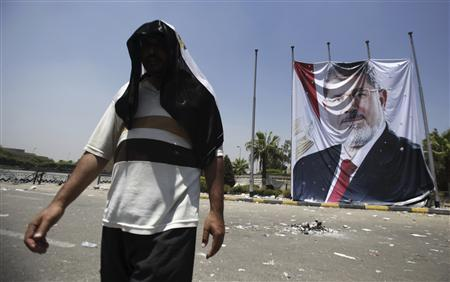 A member of the Muslim Brotherhood and supporter of deposed Egyptian President Mohamed Mursi walks near a huge poster of Mursi, after late night clashes, at the entrance to their campsite near the Tomb of the Unknown Soldier, close to Rabaa Adawiya Square, in Nasr city area, east of Cairo July 28, 2013. REUTERS/Amr Abdallah Dalsh