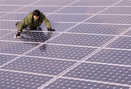 A worker cleans solar panels on the roof of a building in Taiyuan, Shanxi province December 1, 2009. REUTERS/Stringer