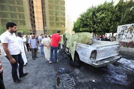 People look at a vehicle belonging to the Libyan army after it exploded in Benghazi July 29, REUTERS/Esam Al-Fetori