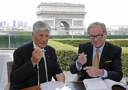 Maurice Levy (L), French advertising group Publicis Chief executive, and John Wren, head of Omnicom Group, hold their pens during a joint signature ceremony in Paris, July 28, 2013. REUTERS/Christian Hartmann