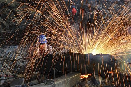A labourer cuts scrap steel at a factory of Dongbei Special Steel Group Co., Ltd., in Dalian, Liaoning province July 24, 2013. REUTERS/China Daily/Files
