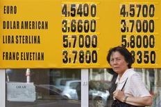 Женщина у вывески пункта обмена валют в Бухаресте 7 августа 2012 года. Доллар поднялся к корзине мировых валют, а австралийский доллар подешевел, после того как глава центробанка Австралии предсказал дальнейшее ослабление национальной валюты и возможность снижения процентных ставок. REUTERS/Bogdan Cristel