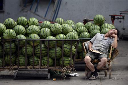 A vendor selling watermelons naps as he waits for customers at a market in Taiyuan, Shanxi province, July 17, 2013. REUTERS/Jon Woo