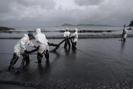 Thai soldiers in white biohazard suits take part in a clean-up operation at Ao Prao Beach on Koh Samet, Rayong July 30, 2013. REUTERS/Athit Perawongmetha