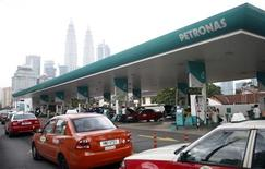 Motorists queue to fill up on natural gas at a Petronas station, with the company's headquarters at the landmark Petronas Twin Towers visible in the background, in Kuala Lumpur July 30, 2013. REUTERS/Bazuki