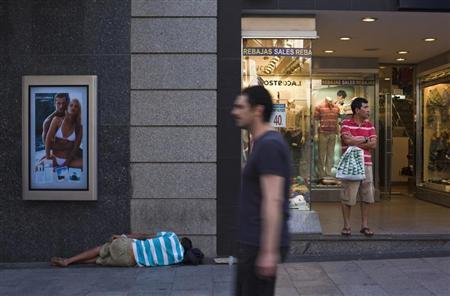 A man (L) sleeps on the street next to a store advertising sales at a shopping district in Madrid July 30, 2012. REUTERS/Susana Vera