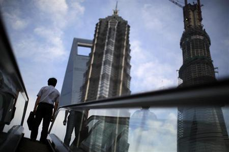 A man rides an escalator near Shanghai Tower (R, under construction), Jin Mao Tower (C) and the Shanghai World Financial Center (L) at the Pudong financial district in Shanghai July 4, 2013. REUTERS/Carlos Barria