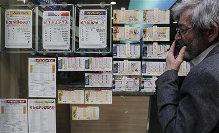 A man looks at lottery tickets outside an OPAP lottery shop in central Athens April 25, 2013. REUTERS/John Kolesidis