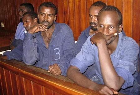 Suspected Somali pirates stand in the dock inside a courtroom in the Kenyan coastal town of Mombasa March 11, 2009. REUTERS/Joseph Okanga